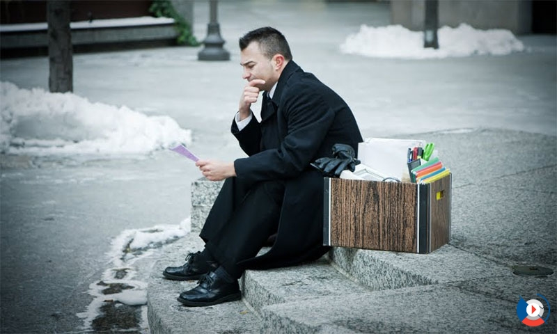 A man sitting on the kerb with his office posessions in a box, having lost his job