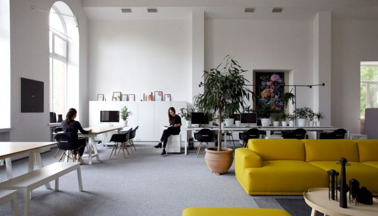 Image of a modern studio style office with two colleagues chatting.