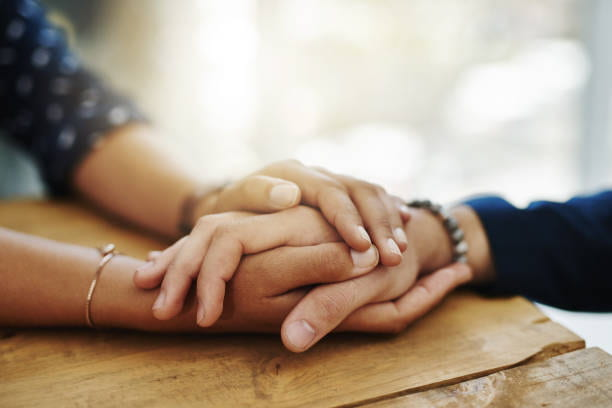 Two hands holding each other in support