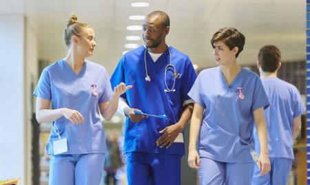 Three health workers walking in a corridor