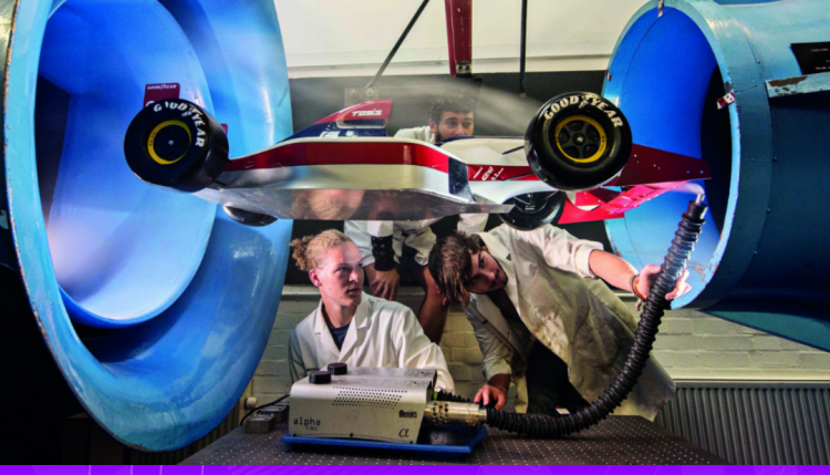 Two engineering students experimenting with a windtunnel