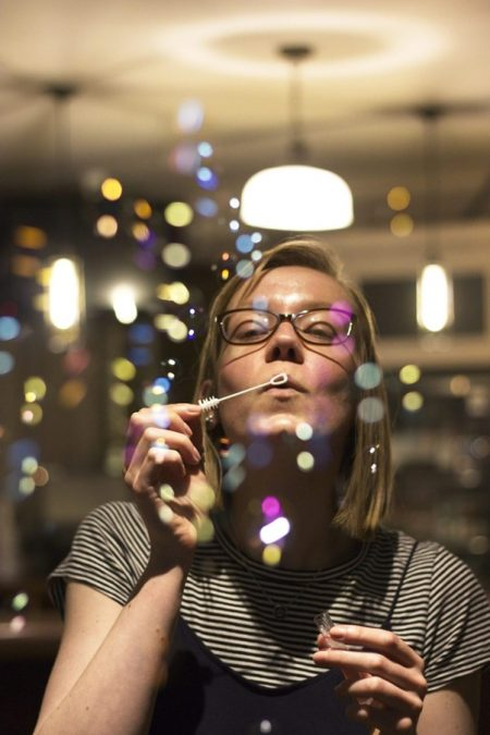 A young woman blowing bubbles