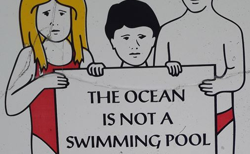 Drawing of three children in swimwear holding a sign bearing the words 'The ocean is not a swimming pool'.