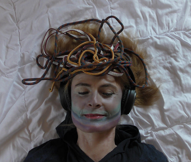 Woman wearing headphones with a tangle of cables around her hair
