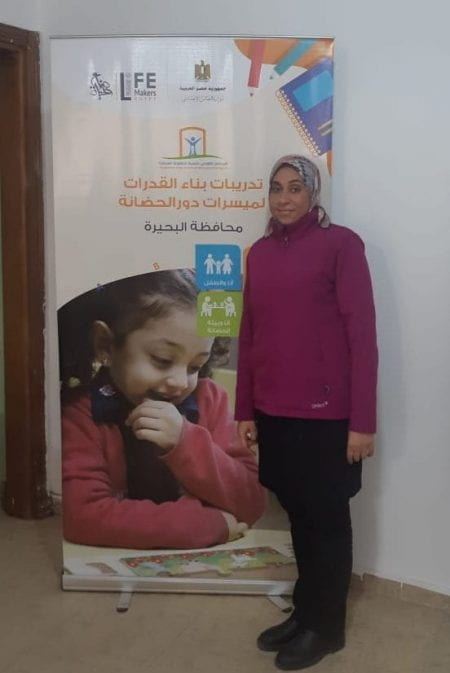 Mawra standing next to a poster