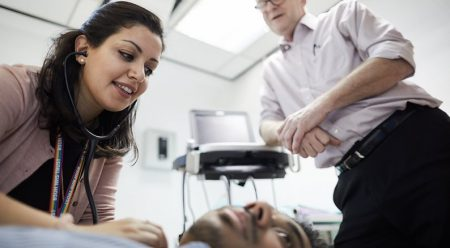 Medical student checking heartbeat under supervision
