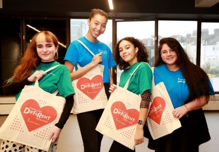 four student ambassadors in coloured shirts with tote bags