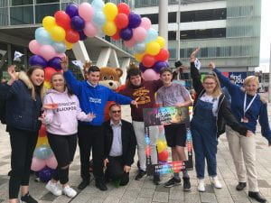 Young people supporting the resilience message, waving under a bunch of colourful balloons