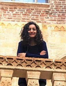 Photo of Buket Kara leaning on a stone balcony