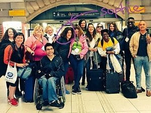 Group photo of people at the train station with suitcases and an arrow pointing to Sophie