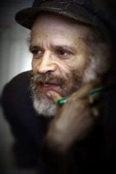 Photo of John Agard looking to the left, hand near face