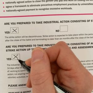 Image of a hand completing a ballot paper