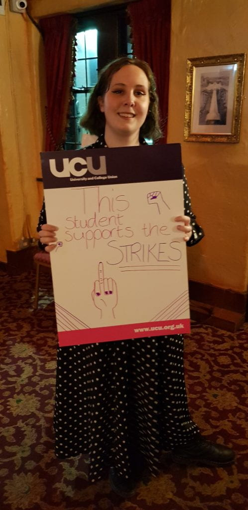"Student holding sign saying ""This student supports the strike"""