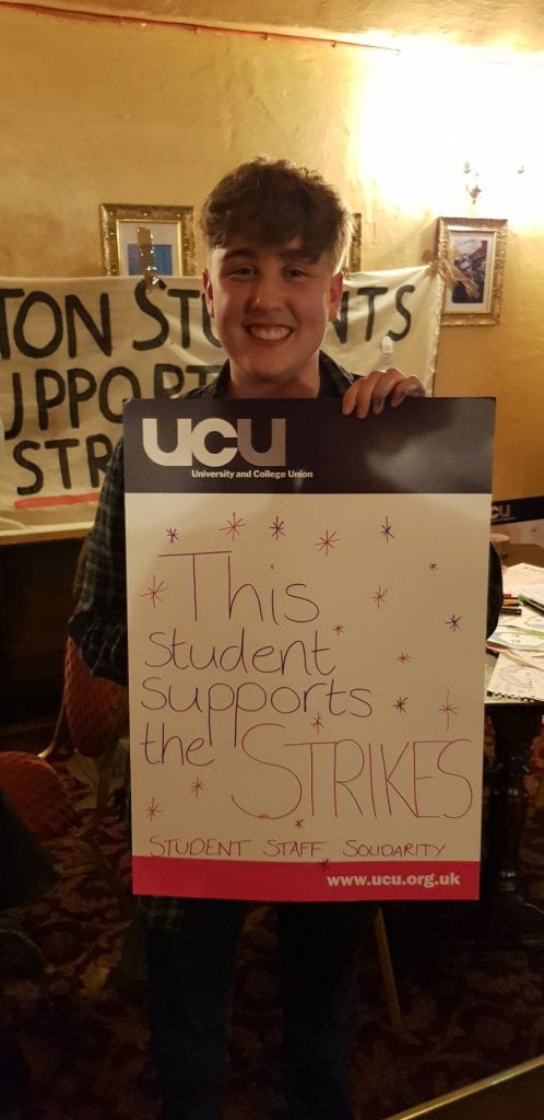 """Student holding sign saying """"This student supports the strike"""""""