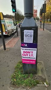 """Placards stuck to lamppost. """"Don't Cut IT"""" and """"Support UCU"""""""