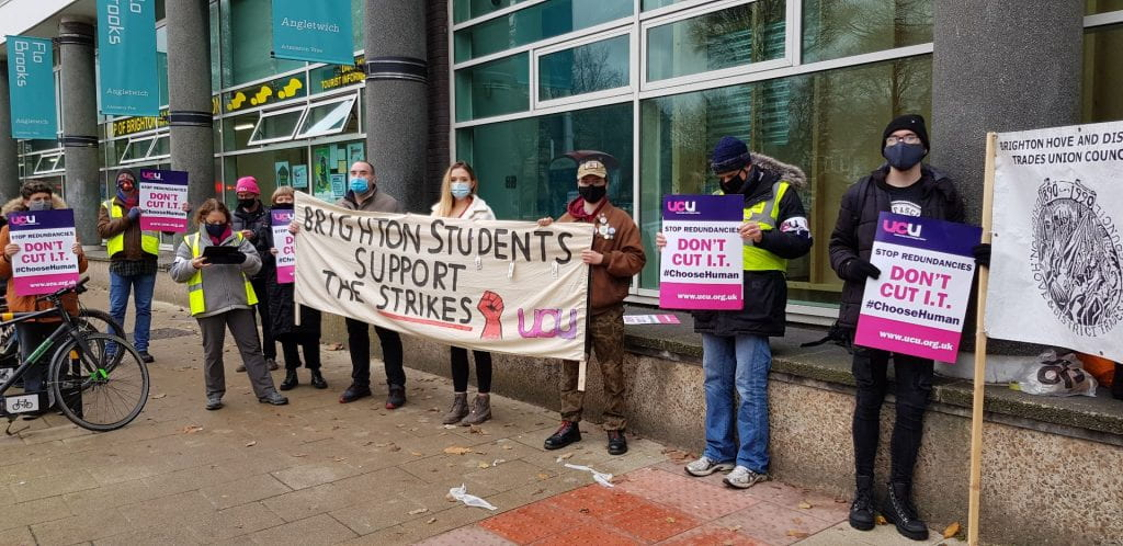 """photo of eight people at a picket line, with three people holding up a banner that reads """"Brighton Students Support the Strikes"""""""