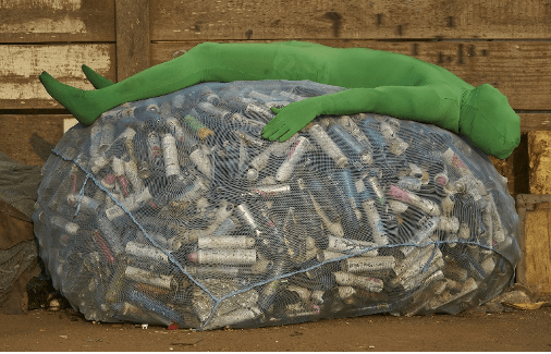 picture of mania a green full body suit laying on a large netted bag full of aerosol cans