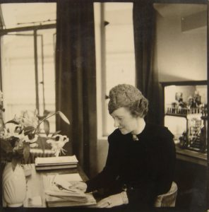 """Alison Settle, Editor of Vogue, early 1930s. Handwritten note at the back of the photograph states: ""Alison at her desk, Editor's room, Vogue, with dolls house in background"""