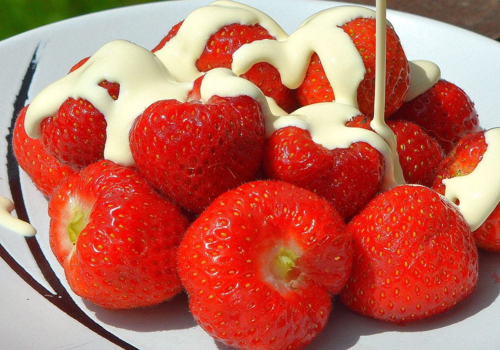 a bowl of fresh strawberries smothered in crean