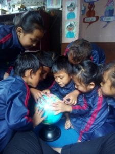 The children looking at a globe