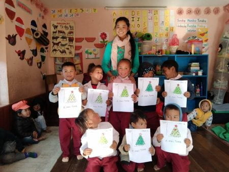 Group of school children holding up their drawings of a Christmas tree