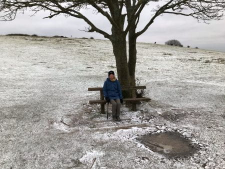 Lorraine sitting under a tree in the snow