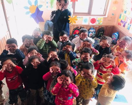 children holding their fingers to their eyes like glasses