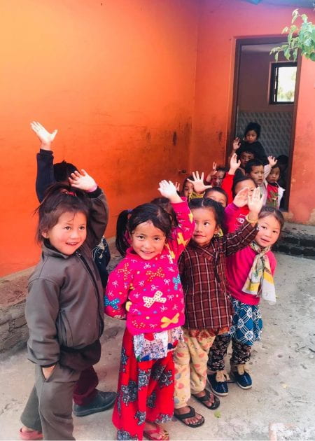 the children waving outside the school