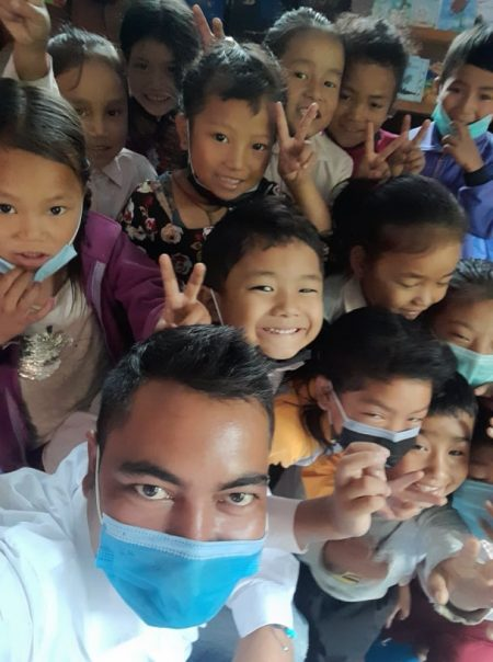 the teacher wearing a mask with the children