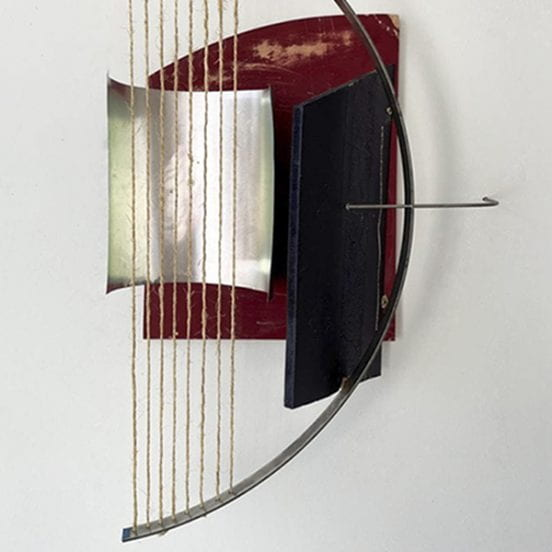 sculpture made from string, metal and wood, hung on wall