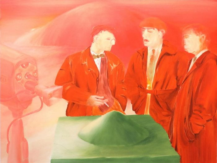 Three men in red suits on red background standing around a green table with green mound on it.