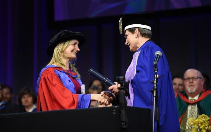 Children's Laureate Cressida Cowell shakes the hand of Vice Chancellor Professor Debra Humphries at the degree ceremony.