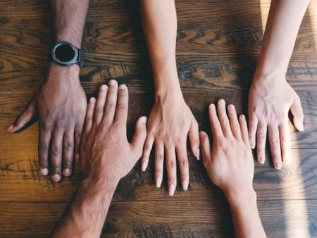 hands lined up on table to represent inclusivity