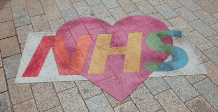 NHS written in chalk on a pavement
