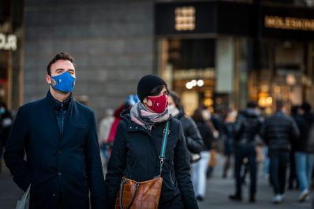 two people walking in the street wearing facemasks