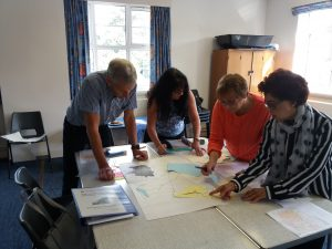 Photo of four people at a table leaning in to look at a large sheet of paper with post it notes.