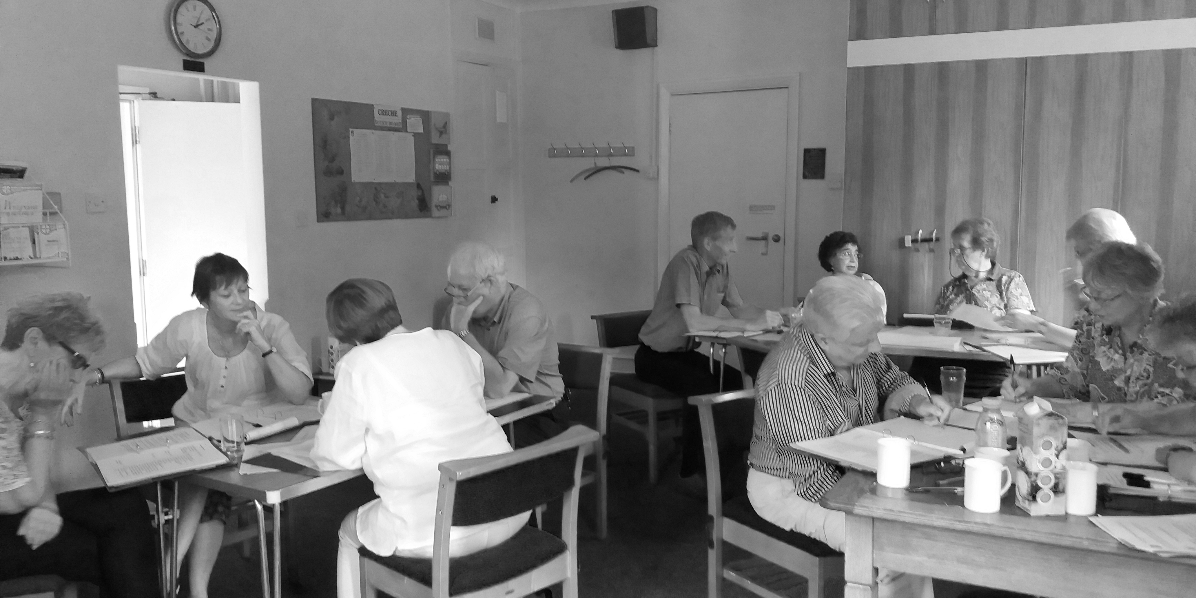 Photo of people sitting at each tables, looking at papers or having conversations