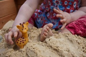 Girl playing in sandpit with a toy giraffe