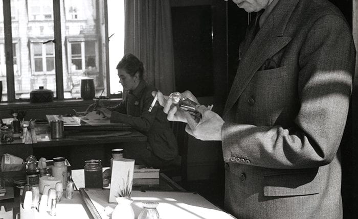 Black and white portrait of Reco Capey inspecting a 3D item with a woman sitting at a desk in the background