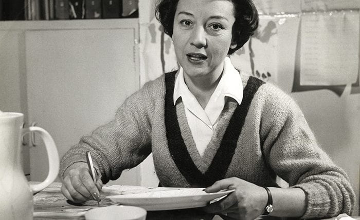Black and white portrait of Lucienne Day hand painting a plate