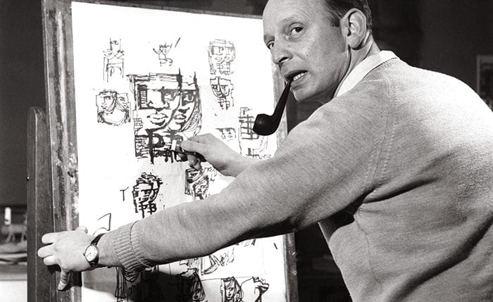Black and white portrait of Abram Games smoking a pipe and drawing on an easel