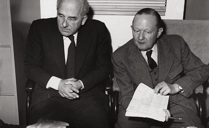 Black and white portrait of Milner Gray sitting down with another man over a pile of papers
