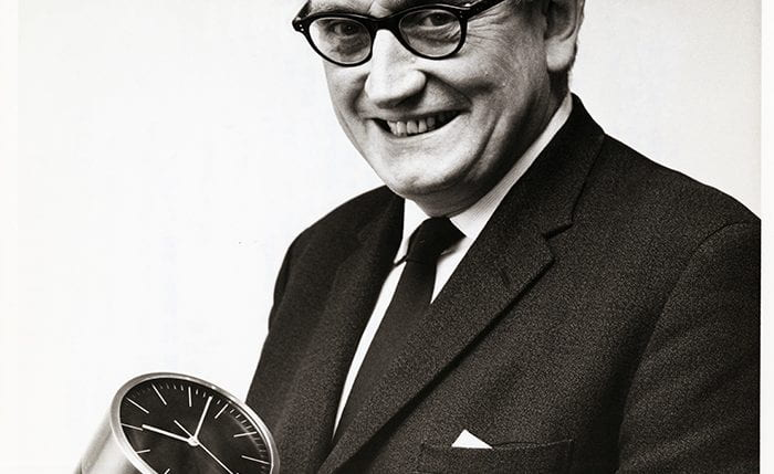 Black and white portrait of Jack Howe smiling at the camera holding a desk clock
