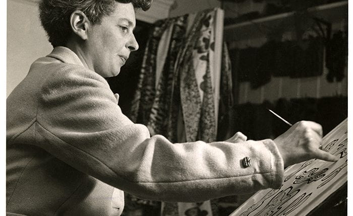 Black and white portrait of Enid Marx drawing over an easel