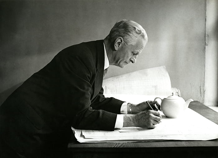 Black and white portrait of Keith Murray leaning over drawings with a teapot by his side