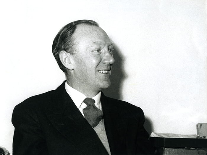 Black and white portrait of Ernest Race smiling at someone just out of shot