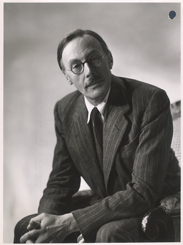 Black and white portrait of Gordon Russell in a pinstripe suit and round glasses