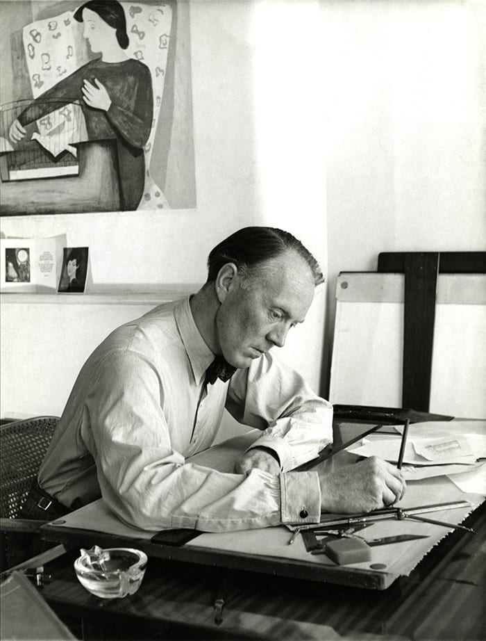 Black and white portrait of Dick Russell drawing at a table