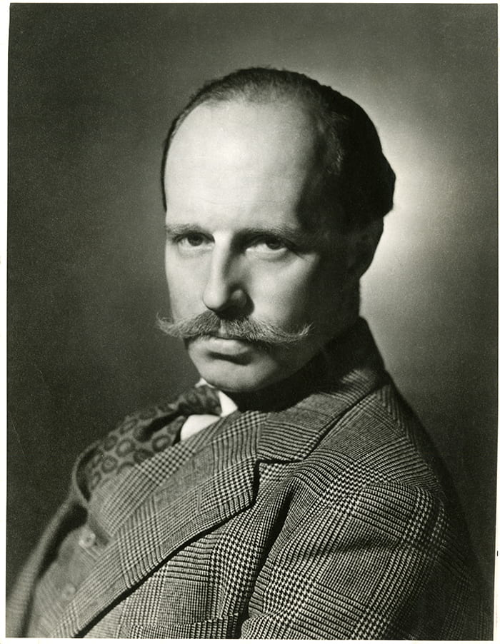 Black and white portrait of Basil Spence sporting a tweed suit and a moustache