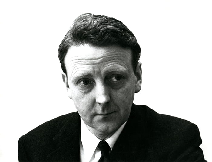 Black and white portrait of Neville Ward from the chest up wearing a suit and tie and looking to the side.